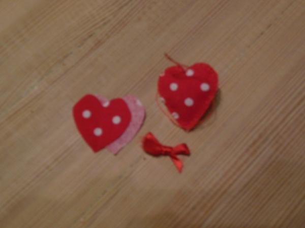 HEr har jeg sydde hjerter sammen, fylt de med noen stoffbiter og satt en slyøyfe i toppen på julehjertet.